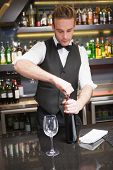 foto of waiter  - Handsome waiter opening a bottle of red wine in a bar - JPG