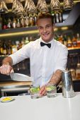 picture of bartender  - Happy bartender making a cocktail in a bar - JPG