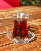 stock photo of vibration plate  - Traditional Turkish glass of tea on wooden table outdoor servise - JPG