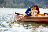 stock photo of boat  - Young attractive wedding couple sharing love in a boat on beautiful lake - JPG