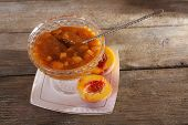 stock photo of apricot  - tasty apricot jam with fresh apricots on wooden table - JPG
