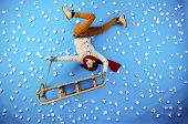 pic of toboggan  - Happy young man on sled having fun against the blue background with snowflakes - JPG