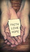 image of faithfulness  - Faith Love Hope stone block in hands with dark background - JPG
