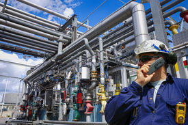 stock photo of gas-pipes  - oil worker with giant pipelines construction - JPG