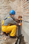 stock photo of plumber  - Home renovation plumber fixing sewerage pipe at construction site - JPG