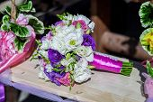picture of swing  - wedding bouquet on a wooden swing swing hanging on a tree branch entwined with flowers - JPG