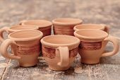 picture of molding clay  - Beautiful clay cups. Life still of the perfectly made clay cups with tiny ornament set in figures on the pottery wooden table
