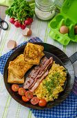 stock photo of scrambled eggs  - Scrambled eggs with bacon and French toast on a cast iron pan - JPG