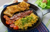 pic of scrambled eggs  - Scrambled eggs with bacon and French toast on a cast iron pan