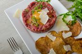 pic of tartar  - Beef tartar and homemade potato chips sprinkled with parmesan shavings and microgreens - JPG