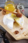 picture of brie cheese  - Gourmet cheese Brie with honey on a cutting board - JPG