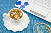 picture of lap  - White cup of coffee with decorated foam and a white lap top on a blue tablecloth - JPG