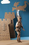 stock photo of berserk  - photo of the boy in medieval knight costume made of cardboard - JPG
