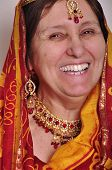 picture of sari  - studio portrait of happy laughing senior woman in traditional Indian clothing sari and jeweleries - JPG