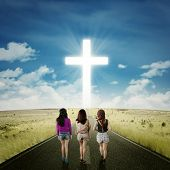image of rear-end  - Rear view of three teenager girls walking together on the road toward a cross on the end of the road - JPG