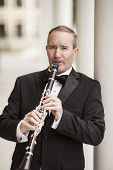 picture of clarinet  - Street performer playing clarinet in tuxedo - JPG