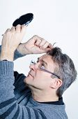 image of dandruff  - Guy checking out his hair with a mirror - JPG
