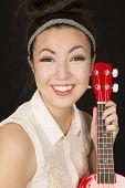 image of ukulele  - Cute Asian American teen girl holding ukulele - JPG