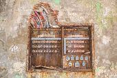 image of fuse-box  - old rusty fuse box with broken dangerous wires above - JPG