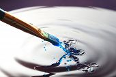 image of dripping  - Blue paint dripping from a paintbrush creating a splatter effect - JPG