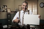 picture of 1950s  - Cheerful businessman showing a blank sign and smiling 1950s office on background - JPG