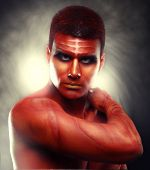 stock photo of adonis  - Portrait of a handsome young man in a red body painting - JPG