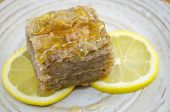 stock photo of baklava  - Juicy baklava on a plate decorated with lemon slices ready to be eaten
