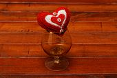 stock photo of glass heart  - Heart and glass on the wood background - JPG