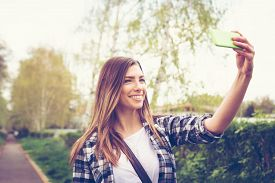 foto of selfie  - Closeup outdoor portrait of beautiful blonde millennial teenage girl taking a selfie with smart phone in park in spring - JPG