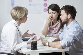 stock photo of insemination  - Couple giving a bribe to speed up their treatment  - JPG
