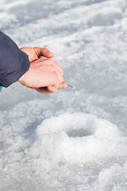 picture of ice fishing  - Winter fishing. Ice fishing. Fisherman on ice fishing from the well, a special winter fishing rod. Fishing in winter. Active, cold, fish, winter fishing tackle. Sport winter fishing/ ** Note: Soft Focus at 100%, best at smaller sizes - JPG