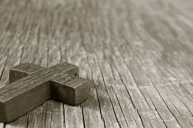 stock photo of christianity  - closeup of a wooden Christian cross on a rustic wooden surface - JPG