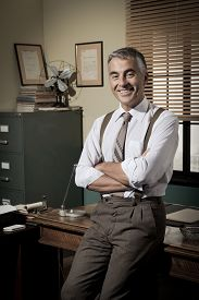 pic of 1950s style  - Confident smiling businessman with arms crossed 1950s style office - JPG
