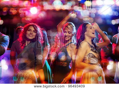 party, holidays, celebration, nightlife and people concept - happy friends dancing in club with holi