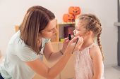 foto of face painting  - Woman painting face of her daughter for the Halloween celebration - JPG