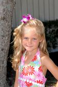 stock photo of flower girl  - a beautiful little girl dressed in a tropical print dress with a flower in her hair and big blue eyes - JPG