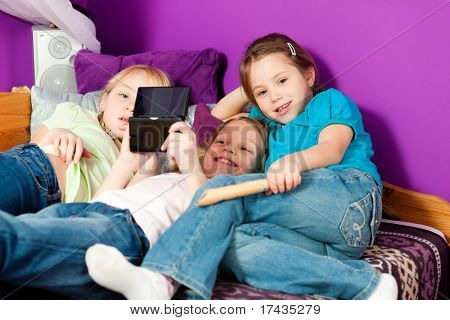 poster of Three children � sisters - playing video games in their room