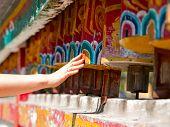 stock photo of karma  - Female hand spinning the prayer wheels for good karma  - JPG