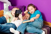 Three children � sisters - playing video games in their room poster