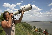 stock photo of pro-life  - professional photographer using his camera with telephoto lens - JPG