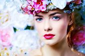 Beautiful romantic young woman in a wreath of flowers posing on a background of roses. Inspiration o poster