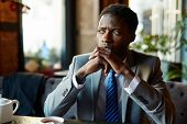 Portrait of handsome African American man wearing business suit looking away to window, pensive and  poster