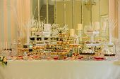 Delicious Sweets On Candy Buffet. Wedding Candy Bar Decoration Setup With Delicious Cakes And Sweets poster