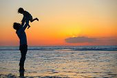 stock photo of beach sunset  - Father and little daughter silhouettes on beach at sunset - JPG