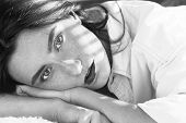 Sad Girl Lying On Sofa In Sun Light Rays Looking At Camera, Monochrome poster