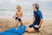 Father Or Instructor Teaching His 4 Year Old Son How To Surf In The Sea On Vacation Or Holiday. Trav poster