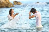 Spontaneous Couple Joking Throwing Water Bathing In The Sea On The Beach poster