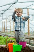 Modern Greenhouse. Small Boy Work In Modern Greenhouse. Modern Greenhouse Worker In Checkered Shirt. poster