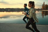 Motivated Couple Of Runners Out For A Run On The Lake At The Sunrise. Young Man And Woman In Sport C poster