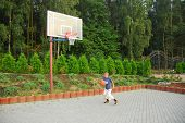 stock photo of bounce house  - teen plays basketball on the playground near house - JPG
